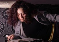 Livro de leitura da jovem mulher em um sofá em uma sala escura imagem de stock