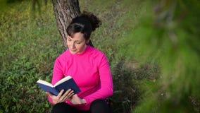 livro de leitura da jovem mulher na natureza vídeos de arquivo