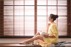 Livro de leitura da jovem mulher perto da janela com cortinas em casa imagem de stock royalty free