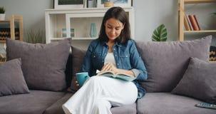 Livro de leitura da jovem mulher que aprecia o copo da terra arrendada da literatura do chá em casa