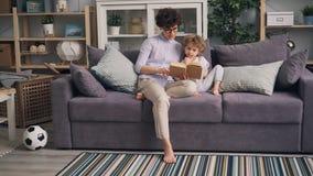 Livro de leitura da jovem mulher a seu filho que senta-se no sofá no apartamento de estúdio junto