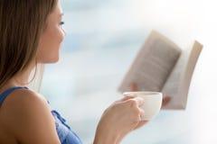 Livro de leitura da jovem mulher, xícara de café da terra arrendada, fim acima fotografia de stock royalty free