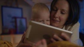 Livro de leitura da mãe em seu dispositivo a seu bebê que encontra-se na cama com imagens do differend e para dar-lhe deleites video estoque