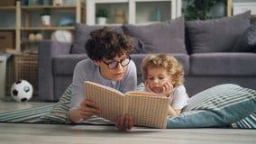 Livro de leitura da mãe da jovem mulher à criança que encontra-se no assoalho na cobertura junto vídeos de arquivo