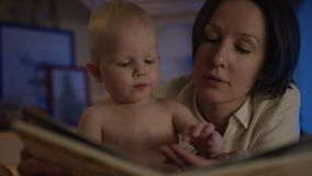Livro de leitura da mãe a seu bebê agradável que encontra-se na cama com imagens do differend e para dar-lhe deleites vídeos de arquivo