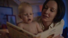 Livro de leitura da mãe a seu bebê que encontra-se na cama com imagens do differend e para dar-lhe deleites com câmera do fluxo vídeos de arquivo