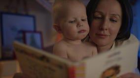 Livro de leitura da mãe a seu bebê que encontra-se na cama com imagens do differend e para dar-lhe perto deleites acima filme