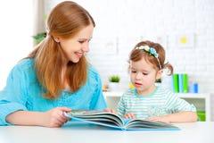 Livro de leitura da matriz e da criança em casa Fotos de Stock