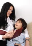 Livro de leitura da matriz e do filho Fotos de Stock