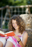 Livro de leitura da menina ao inclinar-se na rocha Fotografia de Stock Royalty Free