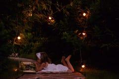 Livro de leitura da menina da criança no jardim do verão da noite com decorações das luzes Imagens de Stock Royalty Free