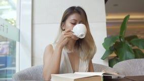 Livro de leitura da menina e café bebendo vídeos de arquivo