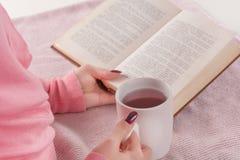 Livro de leitura da menina e chá quente bebendo em casa fotos de stock