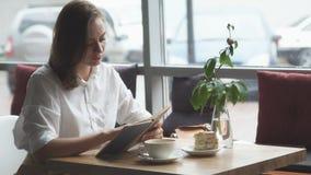 Livro de leitura da menina e relaxamento no café a menina no negócio veste o descanso durante a pausa para o almoço video estoque