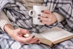 Livro de leitura da menina e xícara de café da terra arrendada e coberto com a cobertura retro fotos de stock