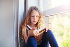 Livro de leitura da menina em casa Fotos de Stock