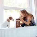 Livro de leitura da menina em casa Foto de Stock