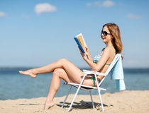 Livro de leitura da menina na cadeira de praia Fotos de Stock Royalty Free