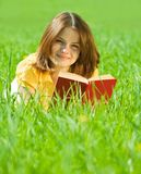 Livro de leitura da menina na grama Imagens de Stock Royalty Free