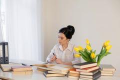 Livro de leitura da menina na tabela no negócio do escritório Fotografia de Stock Royalty Free