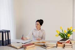 Livro de leitura da menina na tabela no negócio do escritório Fotos de Stock