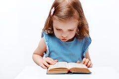 Livro de leitura da menina No fundo branco imagens de stock royalty free