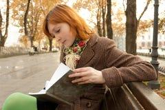 Livro de leitura da menina no parque do outono Fotos de Stock Royalty Free