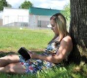 Livro de leitura da menina sob a árvore Imagens de Stock