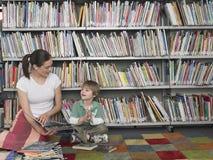 Livro de leitura da mulher ao menino na biblioteca Fotos de Stock