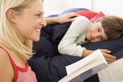 Livro de leitura da mulher ao menino novo no sorriso da cama Foto de Stock Royalty Free