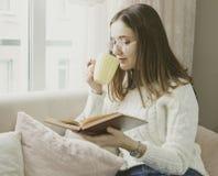 Livro de leitura da mulher com xícara de café em casa na sala de visitas foto de stock