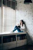 Livro de leitura da mulher e café quente bebendo que sentam-se no sil da janela Fotografia de Stock