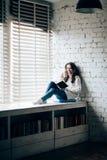 Livro de leitura da mulher e café quente bebendo que sentam-se no sil da janela Imagem de Stock Royalty Free