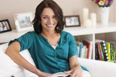 Livro de leitura da mulher em casa imagens de stock royalty free