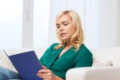 Livro de leitura da mulher em casa Fotos de Stock