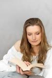Livro de leitura da mulher em casa e relaxando Fotos de Stock Royalty Free