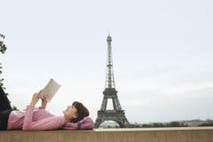 Livro de leitura da mulher em Front Of Eiffel Tower Fotografia de Stock Royalty Free