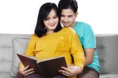 Livro de leitura da mulher gravida e do marido Imagens de Stock