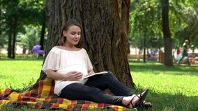 Livro de leitura da mulher gravida no parque, relaxando fora, na saúde e no cuidado pré-natal imagens de stock