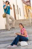 Livro de leitura da mulher na fotografia do homem das escadas Imagem de Stock Royalty Free