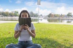 Livro de leitura da mulher no parque na luz de nivelamento imagens de stock
