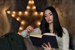 Livro de leitura da mulher no sofá imagens de stock royalty free