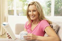 Livro de leitura da mulher nova em casa Fotos de Stock