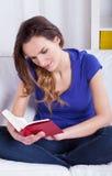Livro de leitura da mulher nova em casa imagens de stock royalty free
