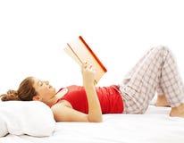 Livro de leitura da mulher nova na cama foto de stock royalty free