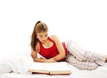 Livro de leitura da mulher nova na cama fotografia de stock