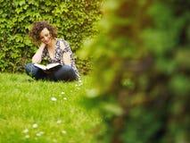 Livro de leitura da mulher nova no parque foto de stock royalty free