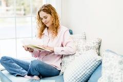 Livro de leitura da mulher pelo indicador Imagens de Stock