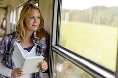 Livro de leitura da mulher que olha para fora o indicador do trem fotos de stock