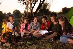 Livro de leitura das crianças pequenas com lanterna elétrica fora fotografia de stock royalty free